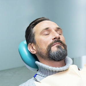 relaxed dental patient reclining in chair with eyes closed