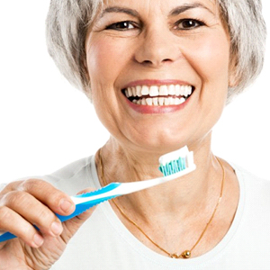 An older woman holding a toothbrush and smiling.