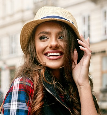 Smiling woman in a hat outdoors