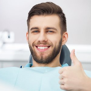 Smiling male patient, thumbs up