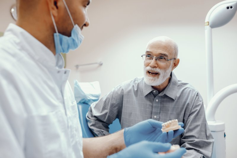 A man asking a dentist about dental implants.