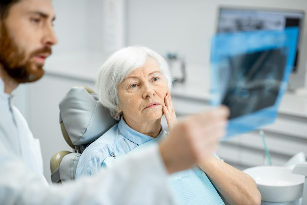 Oral surgeon showing patient X-rays